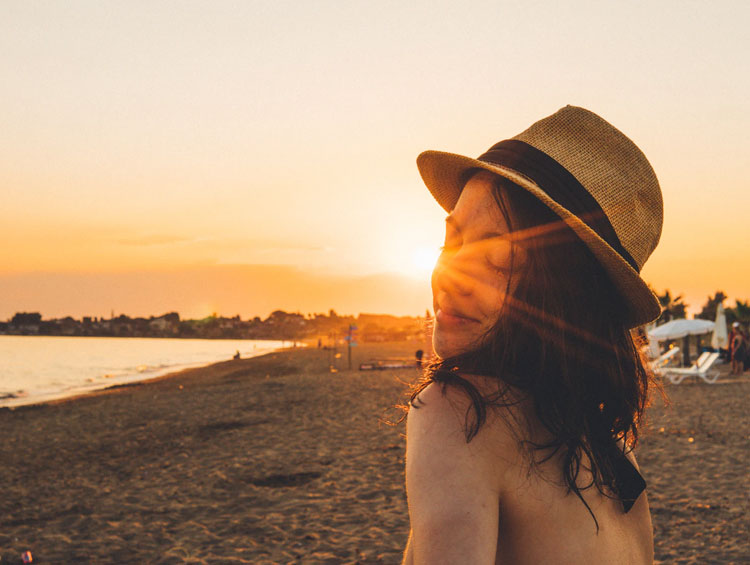 Frau genießt Sonne am Strand