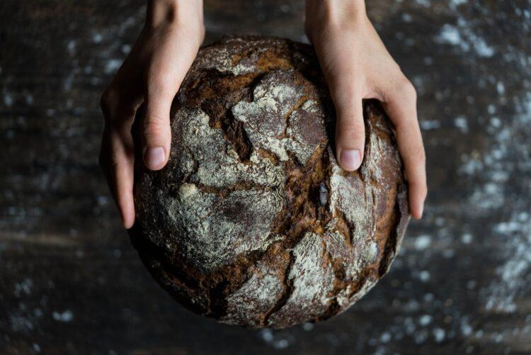 Zwei Hände, die ein Brot halten